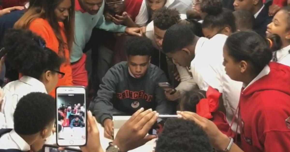 T.M. Landry students surround a fellow student while he opens a college decision letter from Princeton. Videos of T.M. Landry students opening acceptance letters from elite schools have garnered national attention over the past few years. [Photo Credit: CBS News]