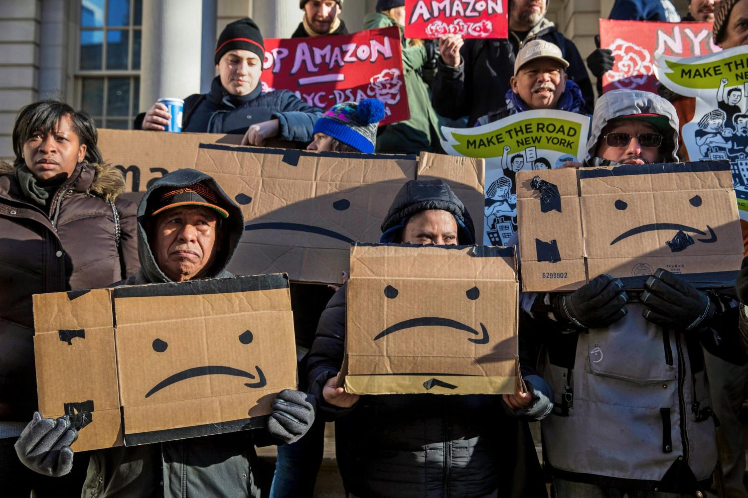 Anti-Amazon protesters gather before a New York Council meeting, displaying their opposition to Amazon's plans for a headquarters location in Long Island City. Amazon ultimately scrapped their plans for the Long Island City headquarters after receiving harsh backlash from lawmakers, progressive activists, and members of the local community. (Credit: Hiroko Masuike/The New York Times)