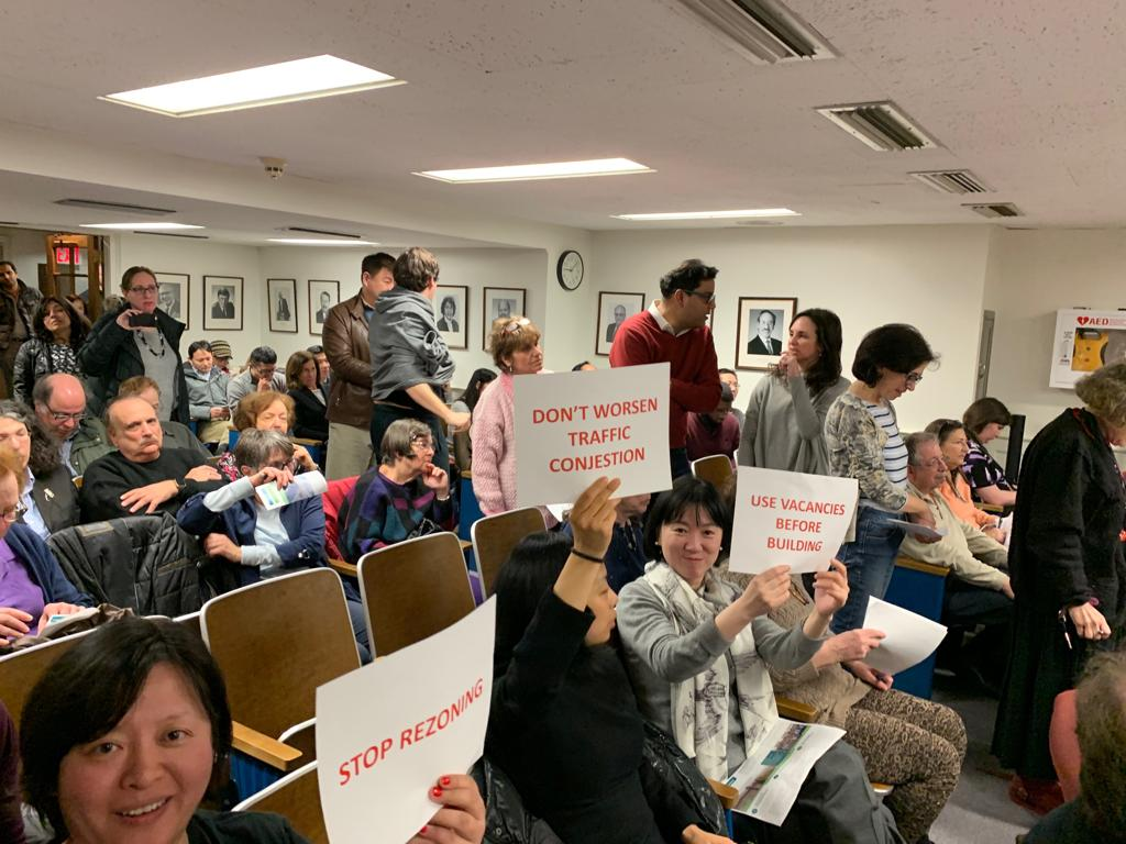 Residents express their frustration with the proposed changes as they hold up signs that say