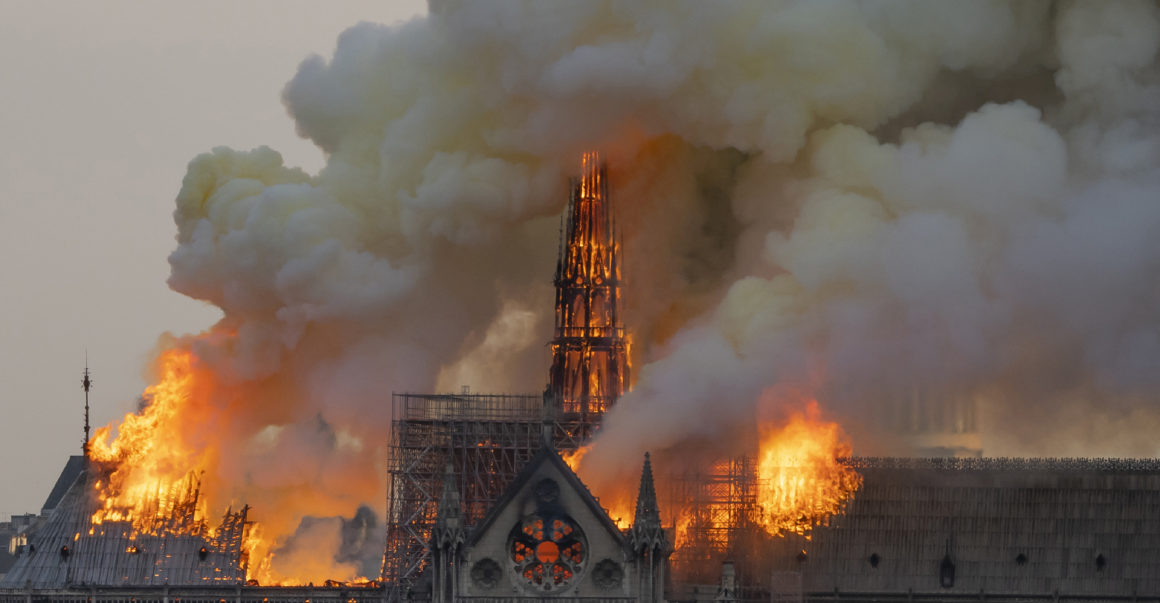 The cathedral spire stands amidst the smoke and fire. Eventually, both the spire and roof collapse on this cathedral, leaving Paris to cope with the aftermath of this tragedy. [Photo Credit: Politico Europe]