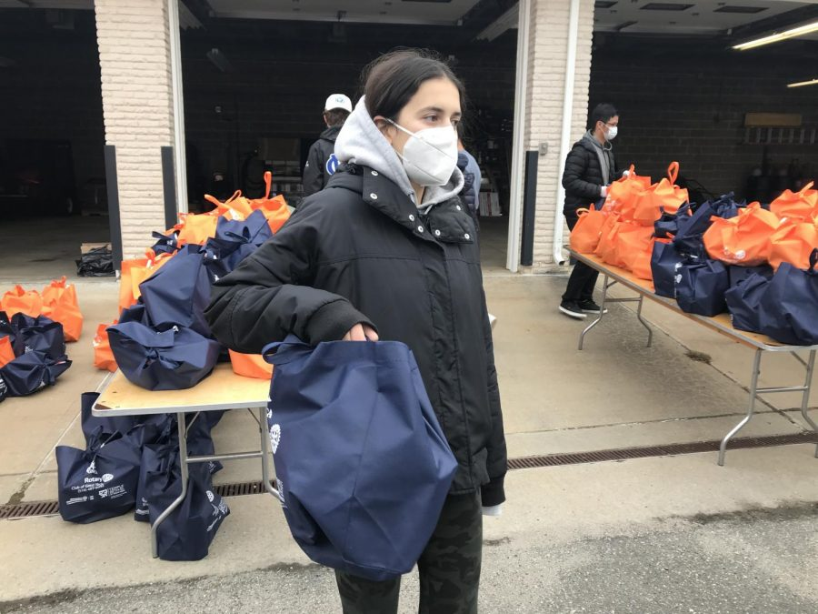 Junior Alexa Nissim carries a fully-packed Thanksgiving meal that will be distributed to a local family.