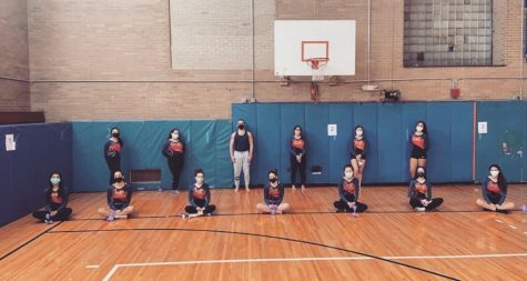 North High gymnasts pose for team photo. The team wears masks and remains socially distanced showing new safety precautions required for this year